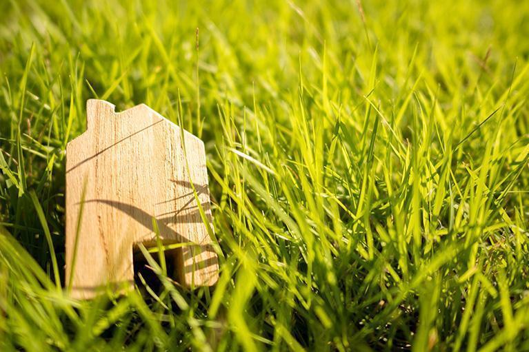 drewniany element przedstawiający dom leżący natrawie